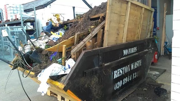 Overloaded skip with fence panel and garden waste